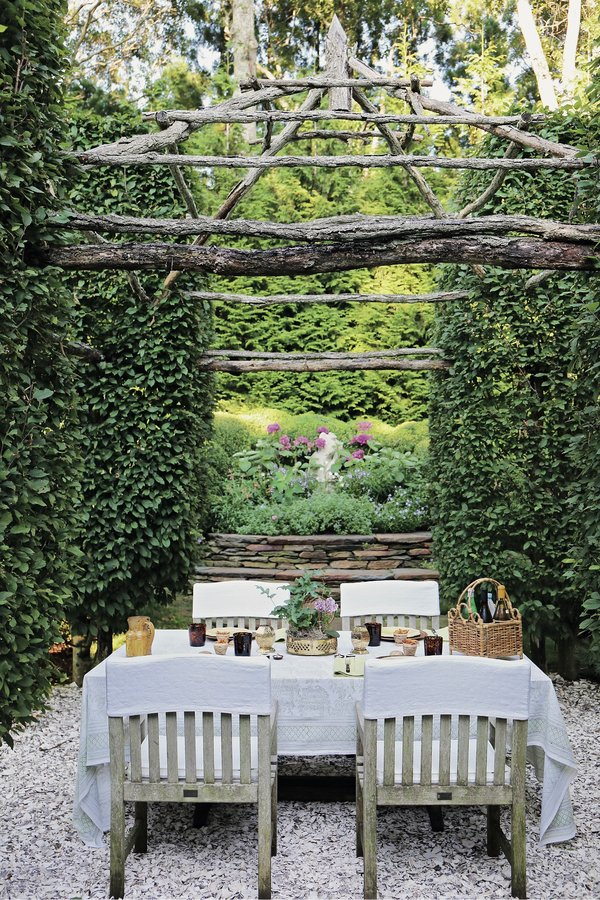 Charlotte Moss designed an intimate dining area in her garden in East Hampton, N.Y., with a floor of crushed oyster shells, hornbeam walls and a ceiling formed by hickory branches.