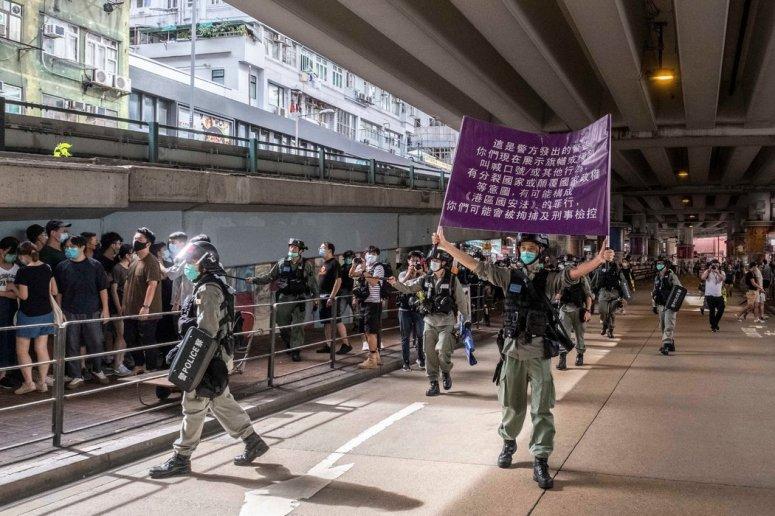 香港警察周三举着紫色旗帜,警告抗议者哪些行为违反《港区国安法》。