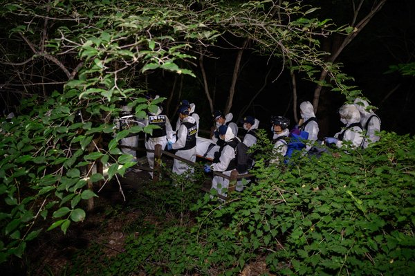 A forensic team carrying Mr. Park's body after it was discovered on a mountain in northern Seoul.