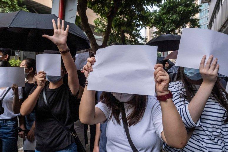 一位被捕抗议者的支持者们举起白纸代替被新国安法禁止的抗议标语。
