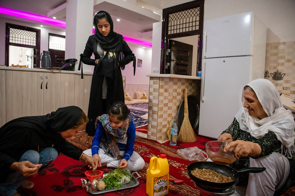 Foroozan preparing lunch with her two daughters, Mozhdah and Mahta, and her mother, Afzal.