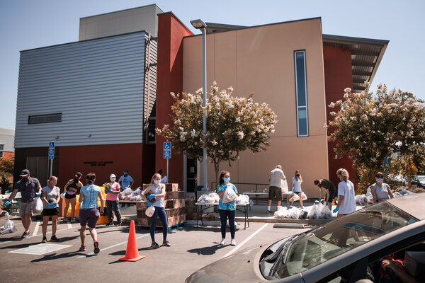 """Volunteers at a food bank in Davis, Calif., last week. """"The path forward for the economy is extraordinarily uncertain,"""" the Fed chair said Wednesday."""