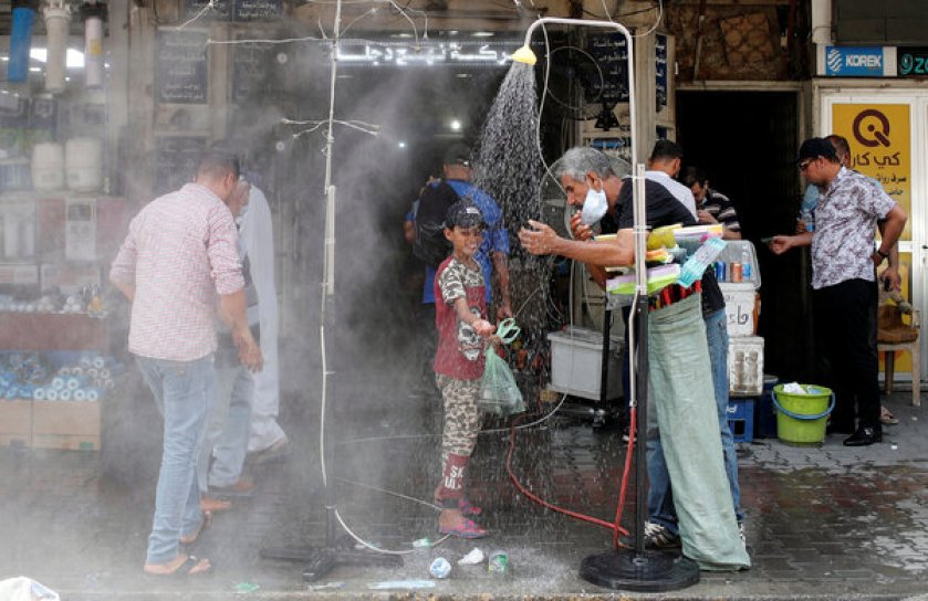 Cooling off under an outdoor shower in Baghdad.Credit...Thaier Al-Sudani/Reuters