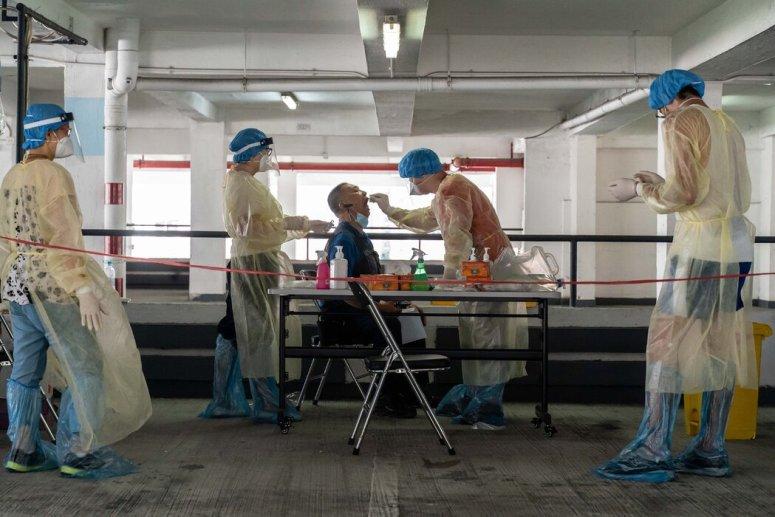 上个月,在香港停车场的一个临时检测点,医护人员在采集一名出租车司机的拭子样本。