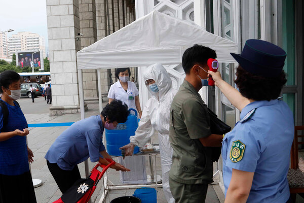 North Koreans disinfecting their hands and getting temperature checks before entering the Pyongyang Railway Station on Thursday.