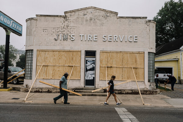 Residents boarding up windows at an auto shop in Abbeville, La., on Tuesday.