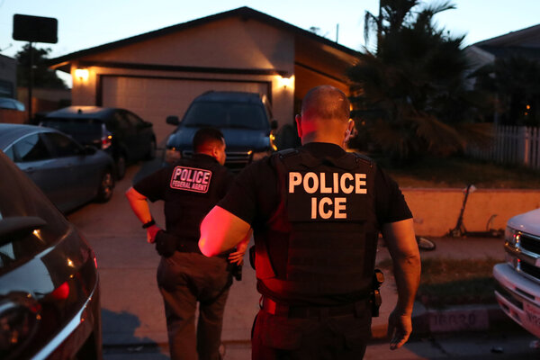 Federal immigration agents arriving to make an arrest at a home in Paramount in March. Arrests that were paused during the pandemic have since resumed.