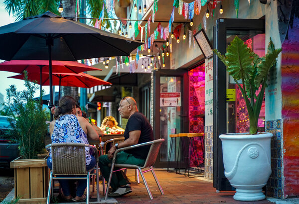 Diners sit outside of a restaurant in the Miami area in August.