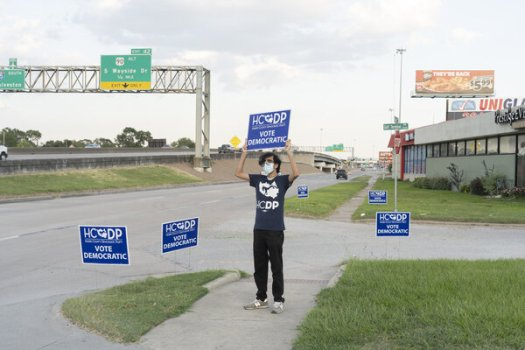 A volunteer with the Harris County Democratic Party directed people to a Houston drive-in event to watch the national convention last month.