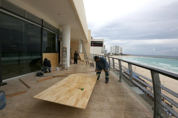 Hotel employees working on Tuesday to protect their businesses in Cancún.