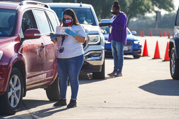 Election workers accepted mail-in ballots from voters at a mail ballot drop-off site in Houston on Wednesday. Gov. Greg Abbott issued an executive order limiting each Texas county to one mail ballot drop-off site.