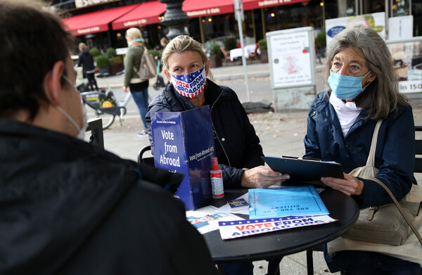 Renee Johnsson of Democrats Abroad, center, and Florian Schiedhelm of Vote From Abroad helped an American register to vote from Berlin this month.