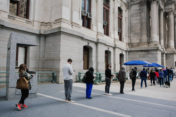 Voters stand in line to apply for and fill out a mail-in ballot in person at City Hall in Philadelphia, on Tuesday.