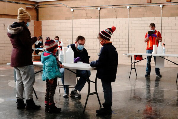 A North Dakota family checks in on a tablet for self-administered coronavirus saliva tests at a testing site.