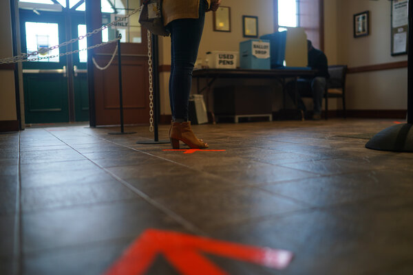 A woman waited at a marked spot as others voted at Little Chute Village Hall in Wisconsin on Thursday.