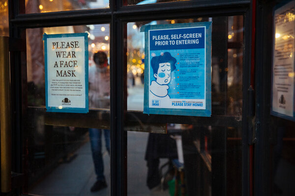 A sign at a restaurant in Chicago urges customers to wear masks and self screen before entering.