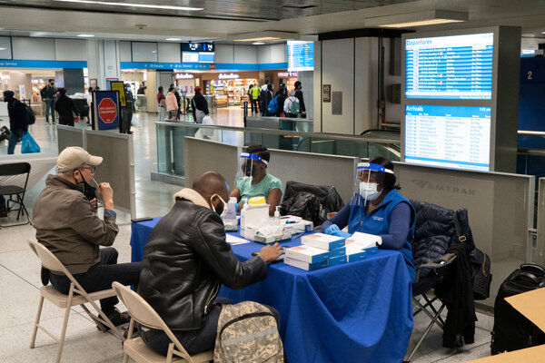 New York City health workers staffed a coronavirus testing station at Penn Station on Monday to screen arriving travelers and inform them about quarantine regulations.