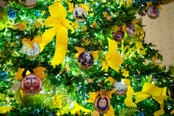 One of the trees in the display features ornaments from each state and yellow ribbons.