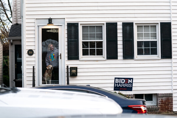 A woman watched from her house as President-elect Joseph R. Biden attended St. Ann's Church in Wilmington, Del.Mr. Biden has transformed the city into a federal-government-in-waiting.