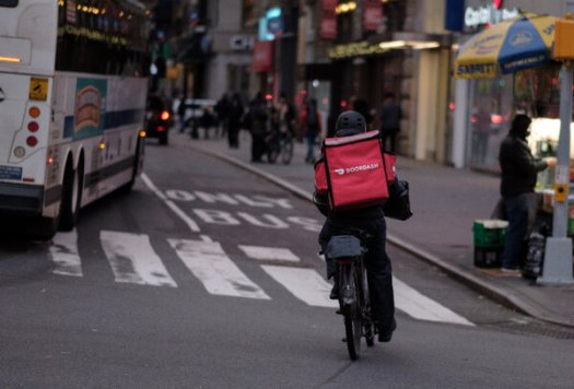 """A DoorDash delivery worker in Manhattan. The company willbegin trading on the New York Stock Exchange on Wednesday under the symbol """"DASH."""""""