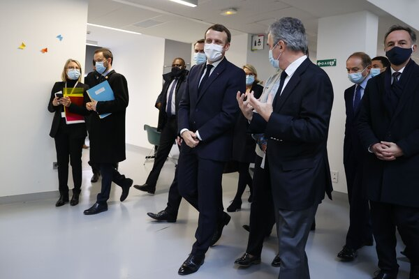 President Emmanuel Macron, center, will work in isolation for the next seven days, the office of the French presidency said on Thursday.
