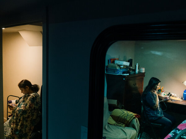 In the dark rooms, Taniya has class while her mother talks on the phone with family in Bangladesh.