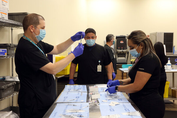 Staff members at Doctors Hospital at Renaissance preparing Covid-19 vaccines for health care workers — and, unexpectedly, for others — in Edinburg, Texas, on Dec. 17.