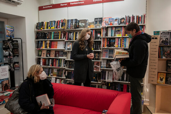 """Samanta Romanese, center, head of the """"Books on the phone"""" initiative, assists a client in the Ubik Bookstore in Trieste, Italy, last week."""