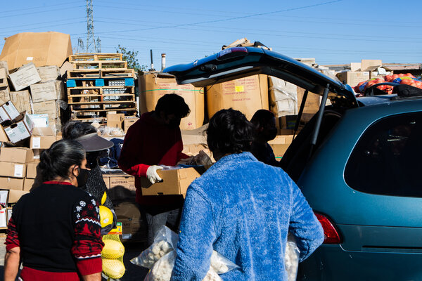 Workers loading up cars at the Vida Life Ministries food distribution center in Bloomington, Calif., on Dec. 19. The pandemic relief bill was welcome news in a tough holiday season for many Americans.