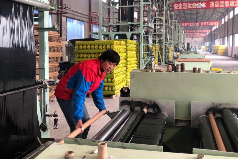 杨晓玲在甘肃省通渭市一家政府补贴的工厂里操作机器,切碎温室用的塑料护根。她用该扶贫计划借给她的钱来支付丈夫的手术费用。