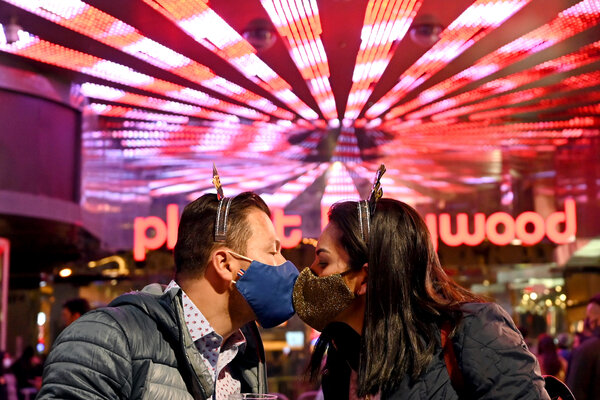 A couple wearing face masks kisses as they celebrate New Year's Eve along the Las Vegas Strip.