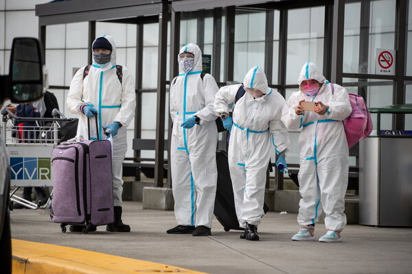 A group of travelers clad from head to toe in protective gear at the Vancouver International Airport in British Columbia.
