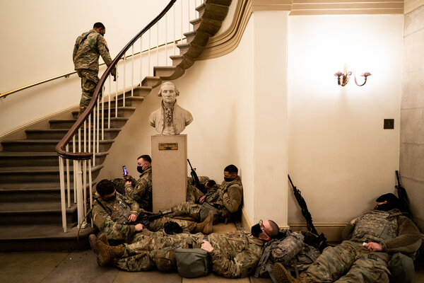 National Guard troops resting in the Capitol Wednesday morning as the House prepared to debate the impeachment charge.