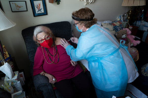 Giving a vaccine shot to a nursing home resident in the Bronx.