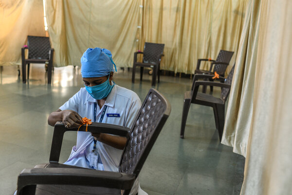 A health care worker decorates a chair at a vaccine center on Friday in Pune, India, where the country's first vaccine doses will be distributed.