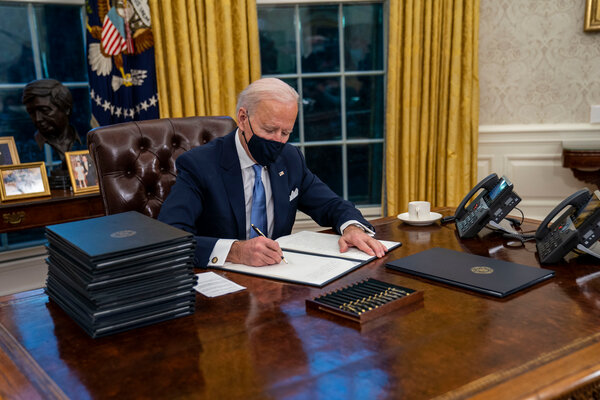 President Biden signing executive orders in his first minutes in the Oval Office on Wednesday.