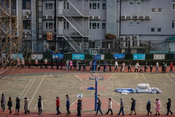 Lining up to be tested for the virus at a school in Beijing on Friday.