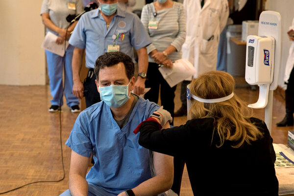A health care worker getting a Covid-19 vaccine in Providence, R.I.