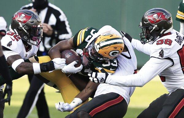 Green Bay Packers running back Aaron Jones is tackled by a trio of Tampa Bay Buccaneers defenders.