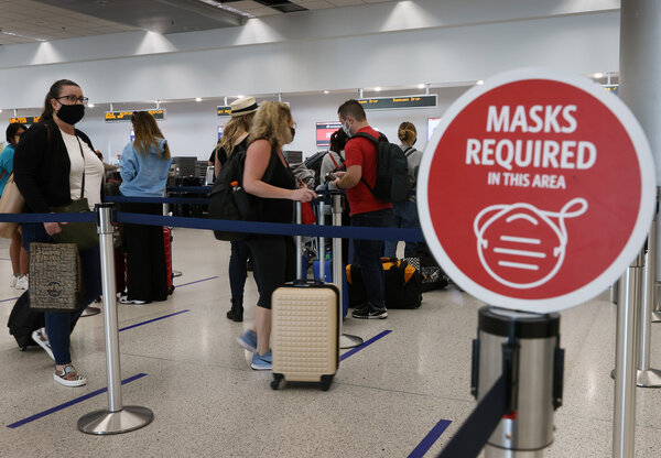 Signs at the Miami International Airport notified travelers on Monday of mask requirements already in effect at the airport. New federal mask rules are due to take effect late Monday night.