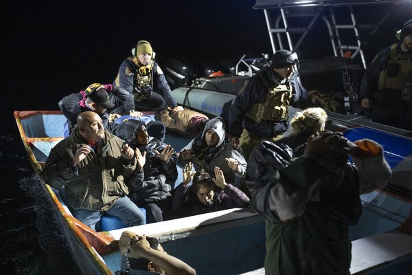 C.B.P. agents transferring migrants to the enforcement vessel, with the smugglers handcuffed at the stern.