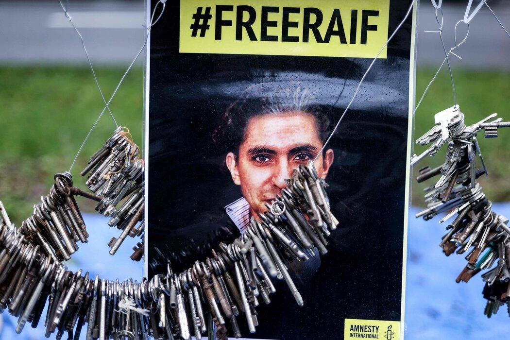 上月布鲁塞尔的沙特大使馆外举行的抗议活动中的拉伊夫·巴达维肖像。