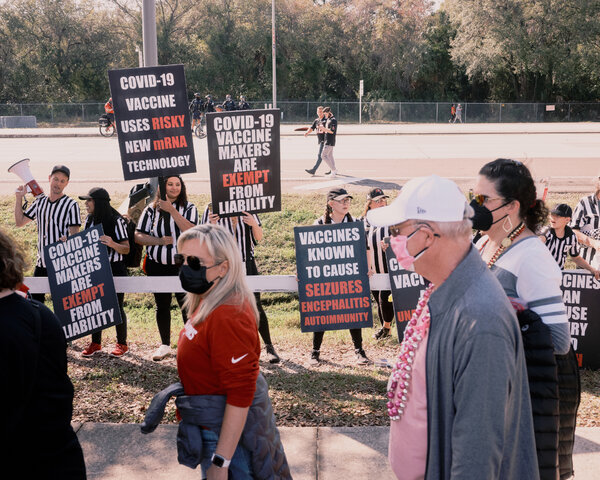Anti-vaccine protesters shouted and waved signs at health care workers in Tampa, Fla., on Sunday as they entered Raymond James Stadium to watch the Super Bowl.