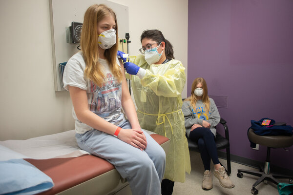 In Houston, Isabelle King, 14, got her second shot from Jallesse Flores during a Moderna vaccine trial this month, as her twin sister, Alexandra, looked on.