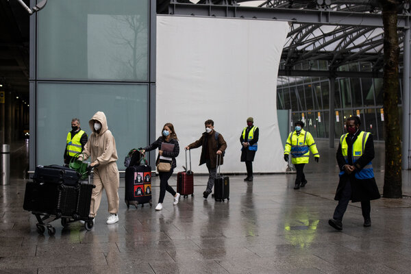 Security personnel at London's Heathrow airport escorted travelers on Monday to buses taking them to compulsory hotel quarantine.