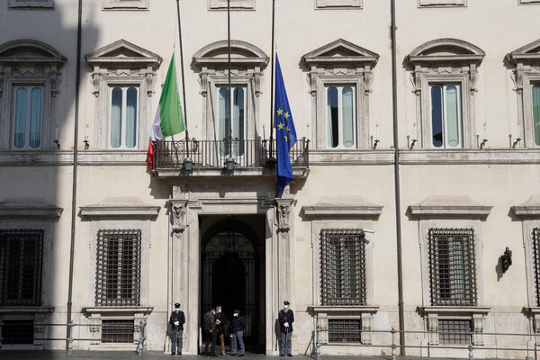 Italian and European Union flags fly for half the staff outside the Chigi palace, the Prime Minister's residence in Rome.