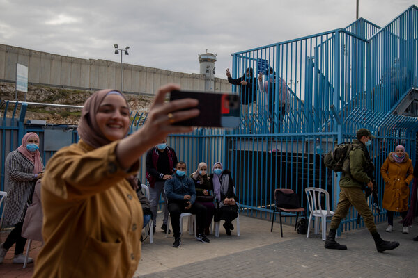 Palestinians take a selfie after receiving the coronavirus vaccine from an Israeli medical team at the Qalandia checkpoint between the West Bank city of Ramallah and Jerusalem on Tuesday.