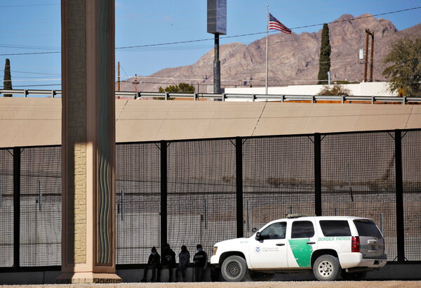 Migrants are detained by a U.S. Border Patrol agent this month as they turn themselves in to request asylum after crossing into El Paso, Texas, as seen from Ciudad Juárez, Mexico.