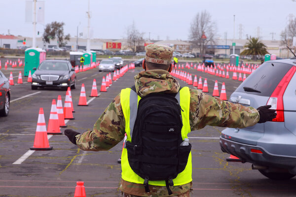 A member of the National Guard directs traffic at a mass vaccination site at the Oakland Coliseum in Oakland, Calif. earlier this month.