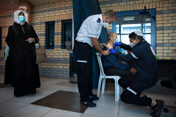 An Israeli medical worker administering the Pfizer-BioNTech vaccine to Palestinians at a checkpoint between the West Bank city of Ramallah and Jerusalem on Feb. 23.